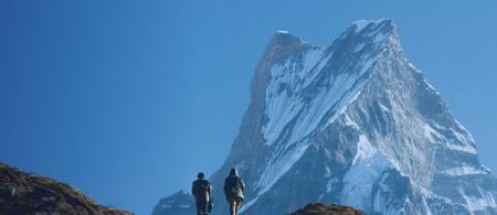 Two people walking on a mountain in Hindu Kush Himalaya. View with a peak behind and a blue sky.